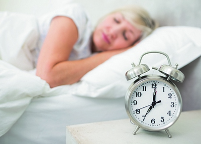Blurred mature woman sleeping in bed with alarm clock in foreground at bedroom